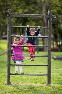 2 kids climbing a wooden wall