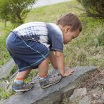 Todler child climbing a rock outside.