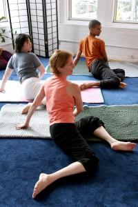 3 students explore rotation in an Awareness Through Movement class.