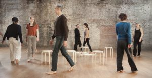 People walk around stools in a studio