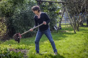 A woman lifts dirt with a garden fork.