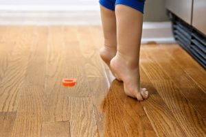 Barefoot toddler on tiptoe with magnets in front of refrigerator.