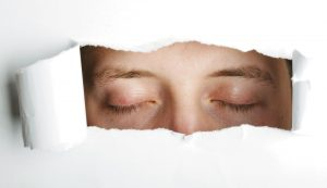 Person with closed eyes revealed through hole torn in paper