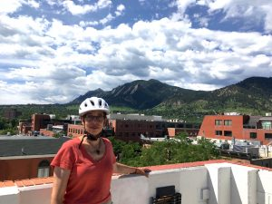 Angela smiling in Boulder with mountains in background.