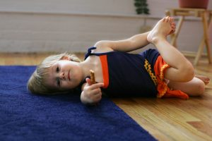 A child holds her foot, lying on floor. Children naturally alternate between learning, doing, and resting.