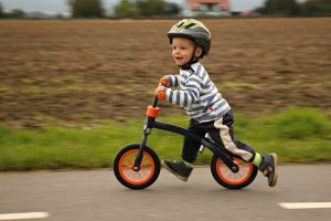 Little boy rides a bike. Lose balance and find it again.