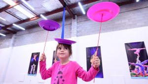 Girl in pink balances spinning plates in her hands and on her head.