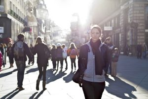 A girl walks quietly on a crowded street